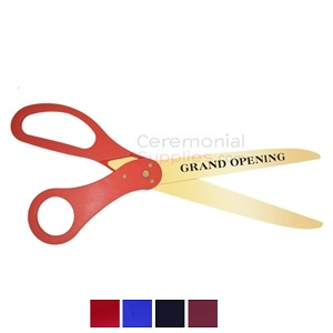 Red handle scissors with golden blades and printed grand opening text.