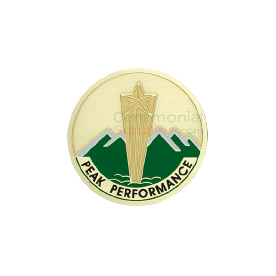 Image of a peak performance medal with a gold shooting star in the center and green mountains in the background