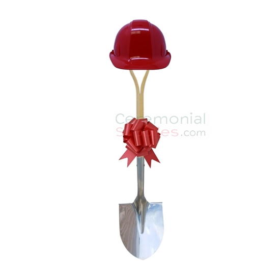 Upright view of red groundbreaking shovel, hard hat and bow kit.