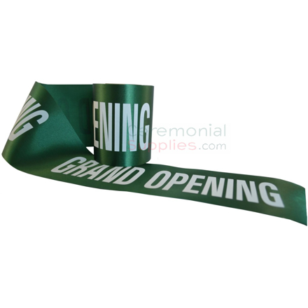 Green printed grand opening ceremonial ribbon posed to show message.