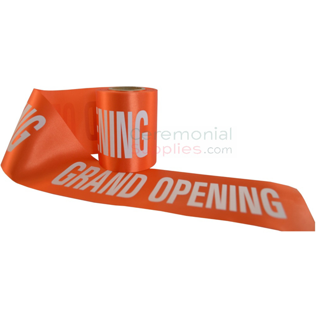 Orange ceremonial grand opening ribbon unraveled to show printed text.