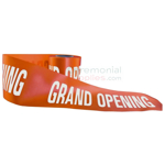 Different angle of orange grand opening ribbon showing text.
