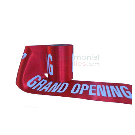 Roll of red grand opening ribbon displaying printed text.