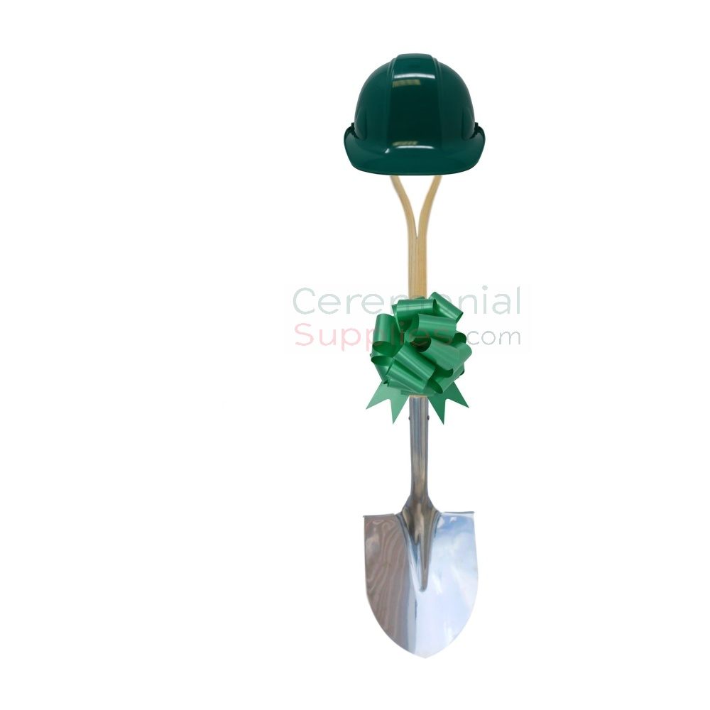 Green shovel, hard hat and bow groundbreaking kit in upright position.